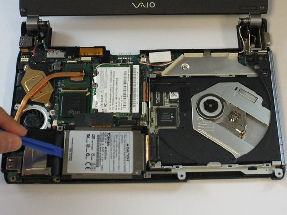 Using the plastic opening tool, pry out  the side of the hard drive.