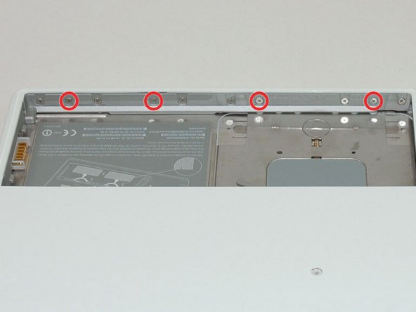 Image 1/1: Remove the four 3 mm indicated Phillips #00 screws from the front wall of the battery compartment. When working from the left, remove the 2nd, 4th, 7th and 9th screw.