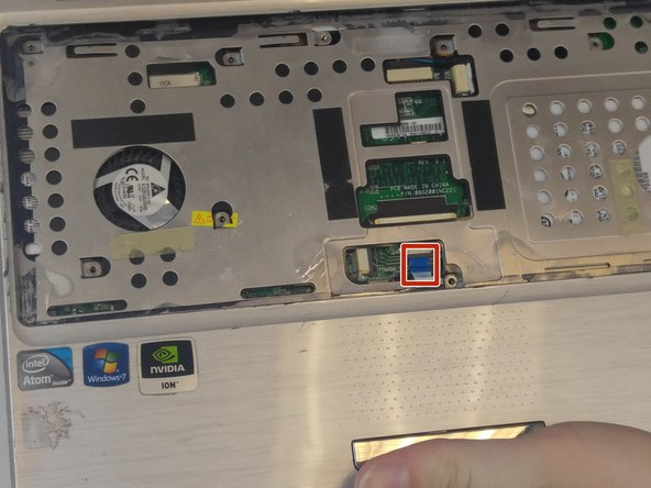 Pull the blue tab for the touchpad connector before removing the cover plate completely.