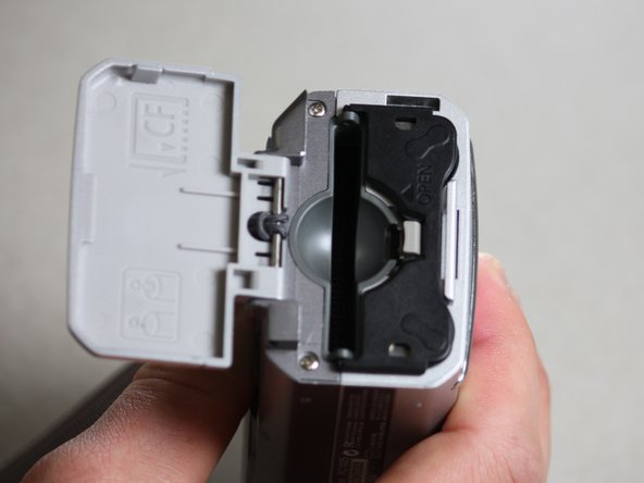 Gently push on the outer battery cover until you hear a click, and then release.
