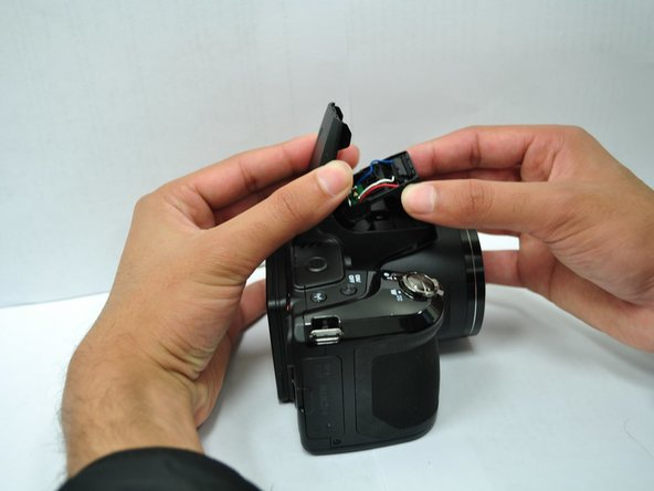 Remove the back case of the flash by lifting it off of the flash.