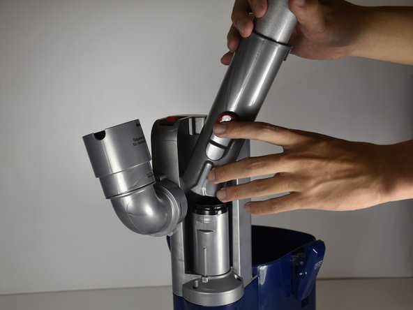 Hold the bottom of vacuum cleaner's handle and its extension.