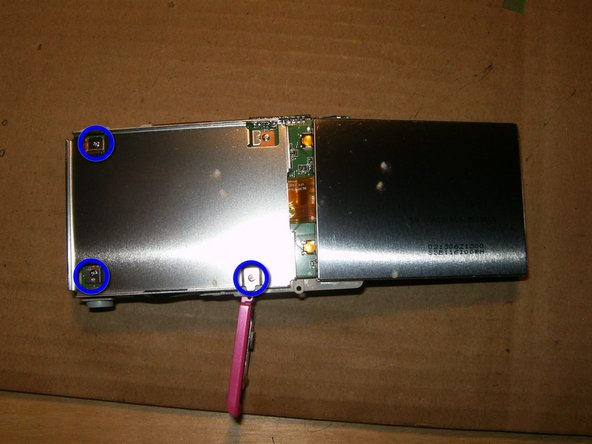 Flip the LCD to the right and out of the frame. Do NOT try to remove it yet.