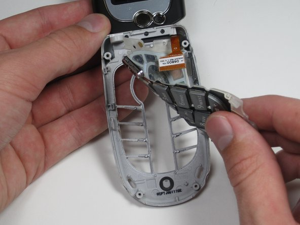 With the phone flipped open, peel the keypad back to remove it from the casing, starting from the bottom.