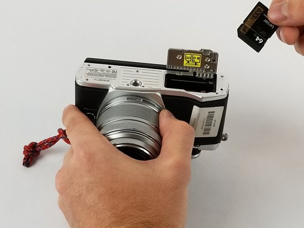 Remove the SD card from the camera by grabbing it with your fingers and lifting away from the camera.