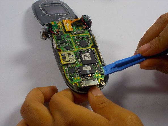Hold the body firmly in one hand. Lift up on the charging aparatus to begin separating the logic board from the front body case./Hold the body of the phone in one hand.  Use a screwdriver to lift up the charging apparatus  separating the logic board from the  front body case.