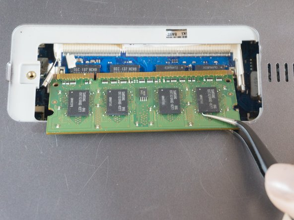 Using the tweezers, grasp the ram card and pull straight out to remove it.