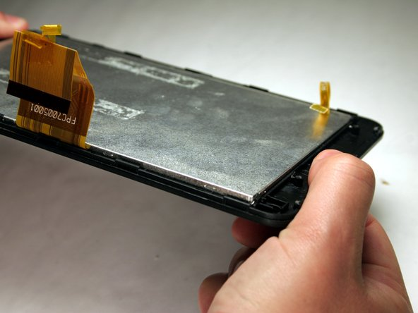 Once the battery and motherboard have been removed, gently bend the screen plate to pop out the metal digitizer that sits on the glass and plastic screen.