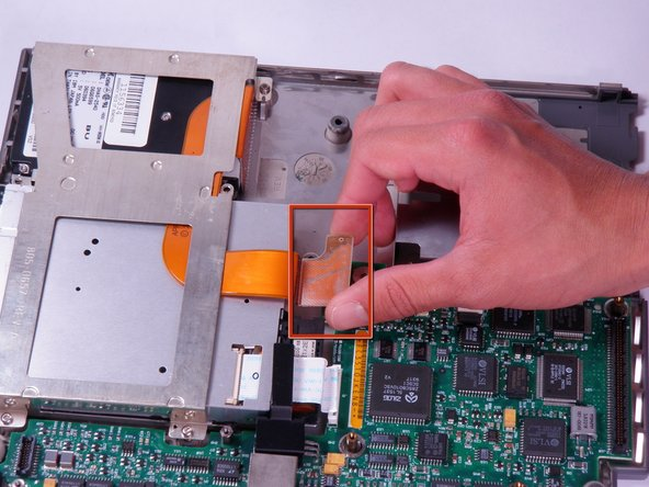Lift up on the orange connector attached to the hard drive until it releases from the motherboard.