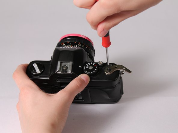 Remove the screw holding the metal component of the lever with a flathead screwdriver.