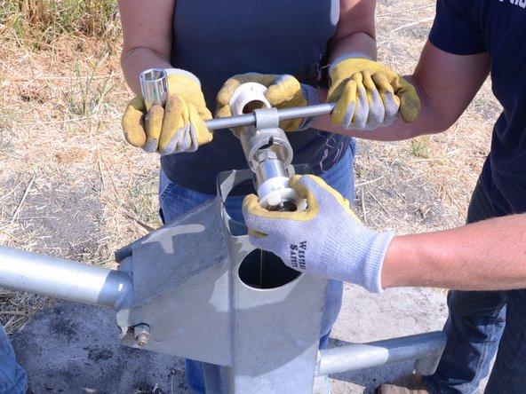 Pendant qu'une personne  soulève la poignée en T, retirez le boulon et les pièces de raccordement.