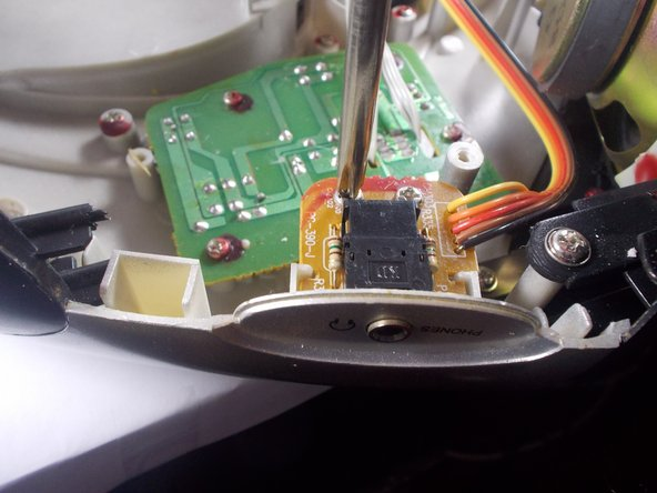 Use a phillips screwdriver to remove the two screws that secure the headphone jack board. Shown to the left.