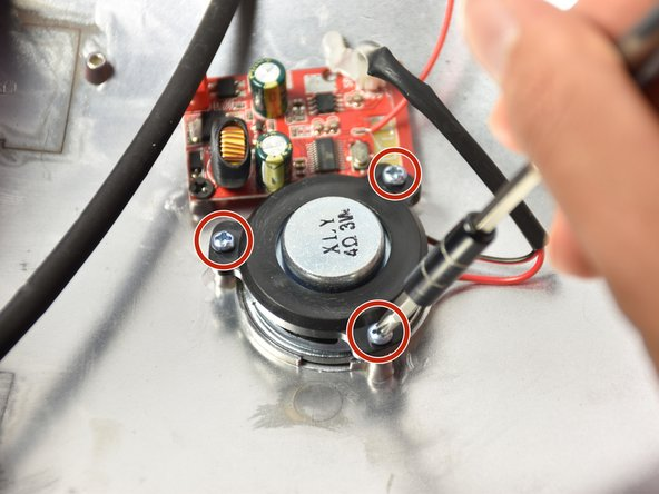 Lift the shell with the speaker grille so the speaker can be accessed.