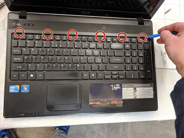 Open laptop then use the plastic opening tool to push in the 6 tabs at top of keyboard.