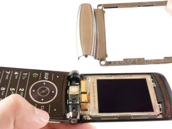 When reassembling, insert the latch on the metal frame into the phone before inserting any other part of the frame.