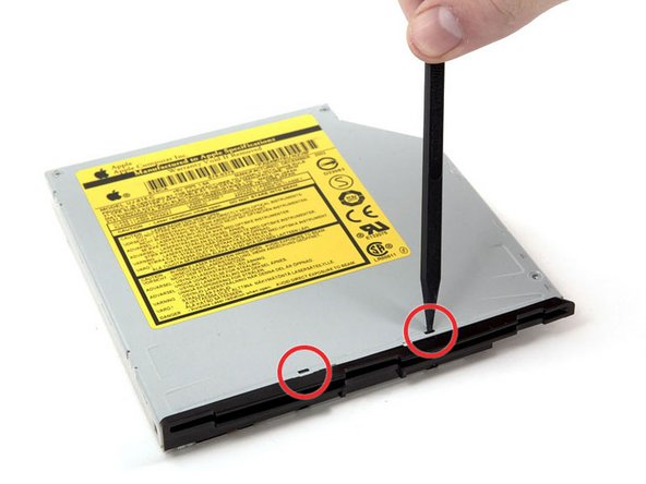 Use a spudger to depress and release the two black tabs on top of the optical drive directly over the bezel.