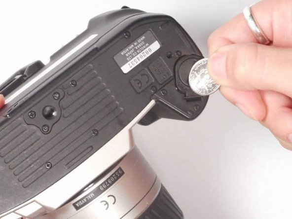 Image 1/1: Use a coin to open the battery compartment of the camera.