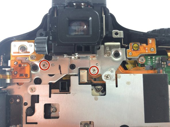 Remove the two #000 Phillips screws, length 2 mm, on the metal panel attaching the eyepiece to the rest of the camera.