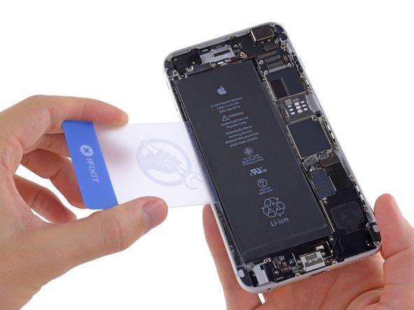 iPhoneを裏返してプラスチックカードをリアケースとバッテリー左横の間から差し込みます。