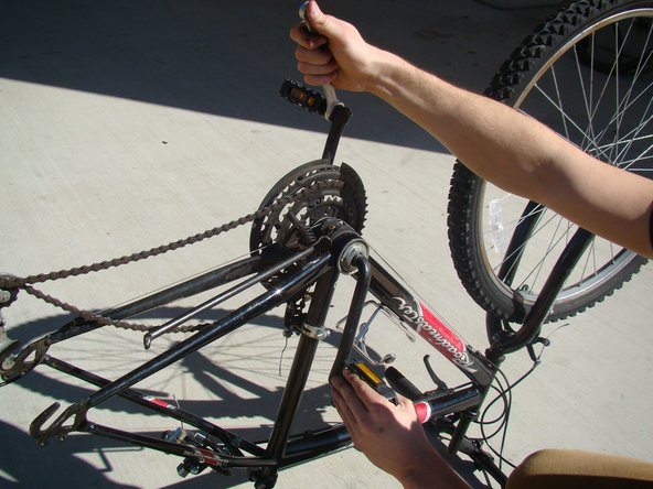 Using a 15mm open-end wrench, brace the opposite pedal with your other hand and remove the pedal nut from the crank arm.
