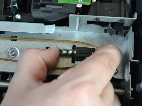 Using one hand, loosen the carriage belt around the wheel by compressing the spring against the wheel.