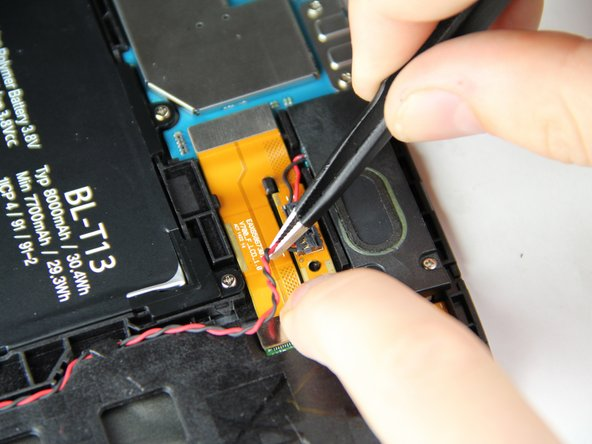 Image 1/2: While holding the orange ribbon cable in place with your finger, grab the wires and pull upwards to disconnect the speaker from the device.