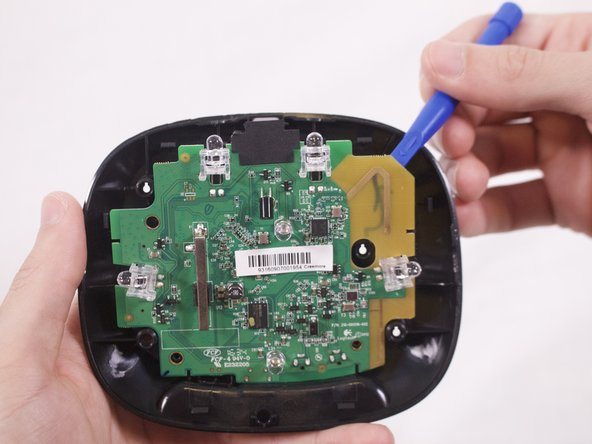 Insert the plastic opening tool behind the motherboard on the gold section, which is to the right of the sensor.