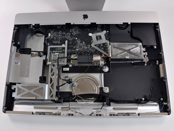Removing the massive logic board requires two hands. With the RAM cavity opened underneath the iMac try to help pushing the logic board with the thumb towards the upper part (towards the isight camera), to ease the release of the logic board.