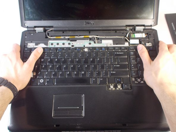 Grasp the laptop with both hands as shown.