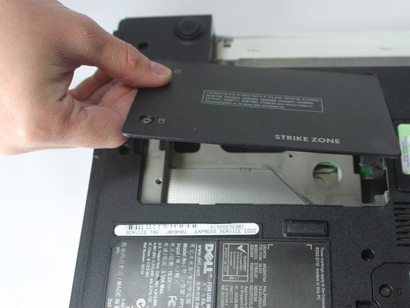 Using your fingers, open and remove the access door from the laptop, exposing the hard drive underneath.