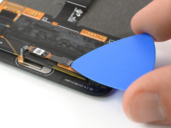 Use an opening pick to open the black flap of the home button ZIF connector.