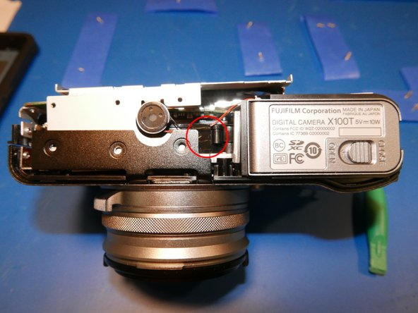Image 1/2: The speaker is held into place by double sided tape. Pull it off the steel frame and move it toward the bottom of the camera