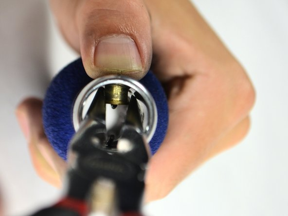 Once grasping the golden fastening button tightly with small needle-nosed pliers, carefully and slowly pull it out of the handle bar.