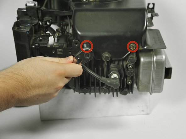 """Use a socket wrench with a 3/8"""" socket to remove the two 20mm screws on the front of the engine shield."""