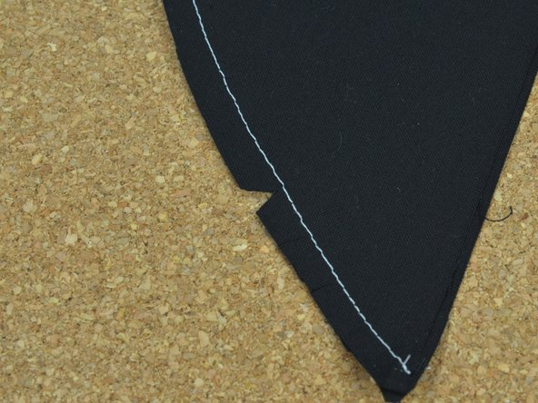 Image 2/3: Continue cutting small triangles along the length of the fabric.