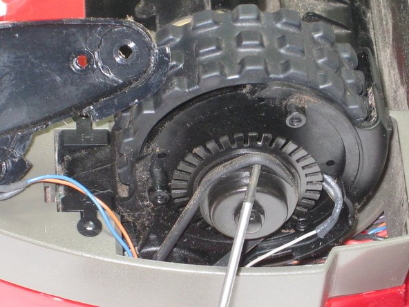 With a screw driver, gently remove the drive belt from the gear.