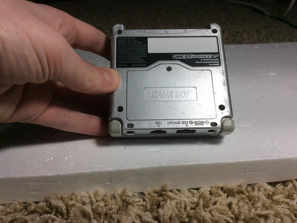 Turn your GBA upside down so that the battery compartment is facing up.