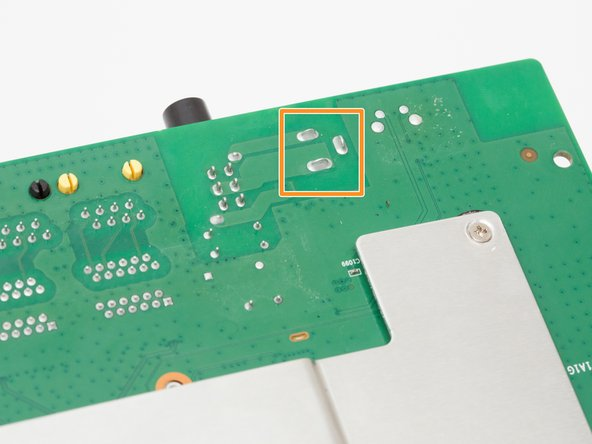 Locate the 3 solder joints that connect the power adapter port to the motherboard.
