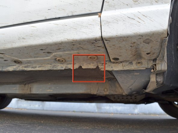 Image 1/2: Begin by locating the jacking point. It is on the passenger side of the car, just behind the front wheel.