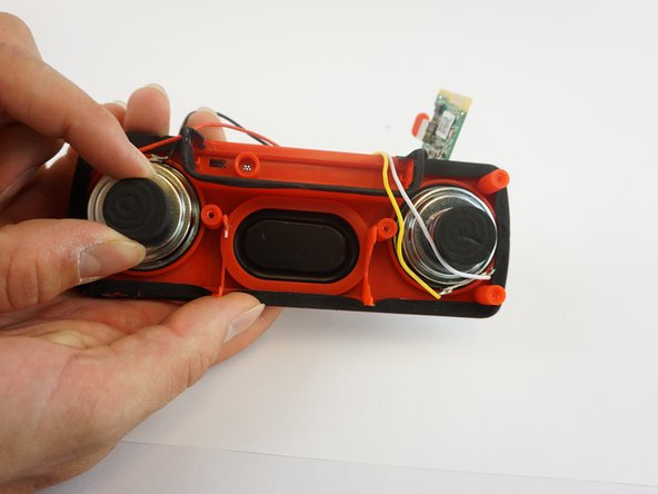 Grab the back piece of the speaker and gently pull upward.