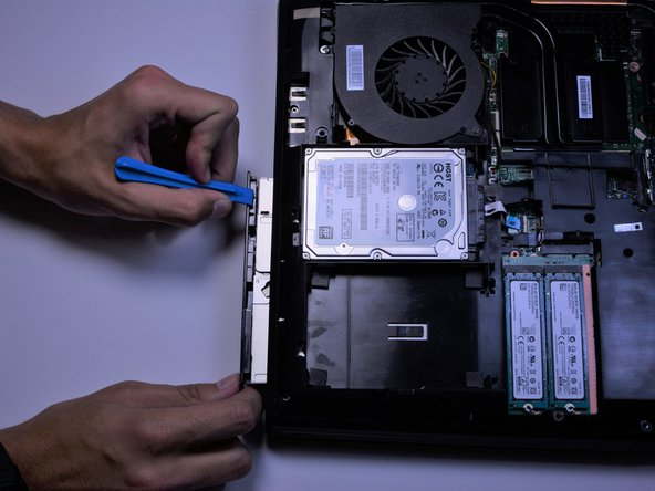 Using the plastic opening tool, pull out the CD drive.