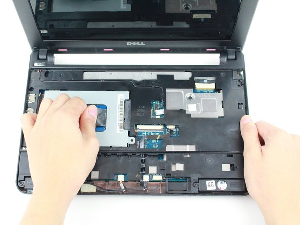 Pull on the black tab and slide the hard-drive cage toward the USB port on the left side of the device until its comes free and carefully lift out of device.