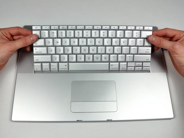 Image 2/2: Maintaining your hold on the keyboard, lay the casing flat and gently bow the keyboard until the two tabs on either side of the keyboard come free.