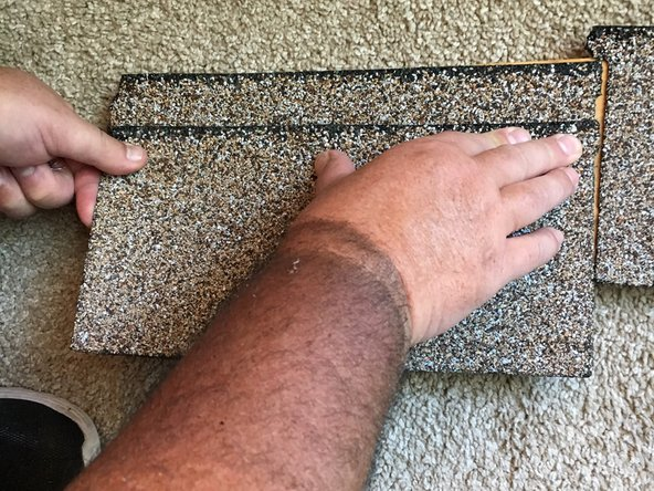 Press down the edges to lock the shingle in place.