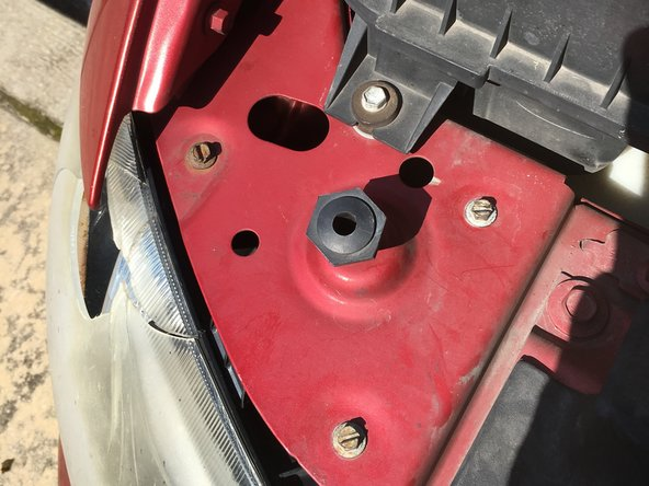 Image 1/2: Remove the three bolts holding the headlight in place. *Note* If they are rusted like mine were, be prepared to use some elbow grease.