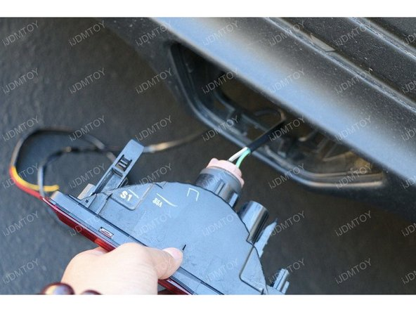 Remove any plastic clips that hold the rear plastic cover over the bottom of the trunk. Route the wires from the tail light assembly through the bumper and into the trunk area.