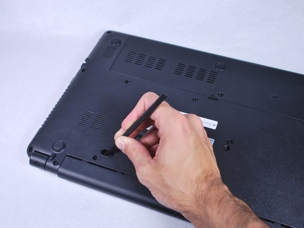 To release the battery, depress the battery release with a nylon spudger. Hold the latch down and slide it over.