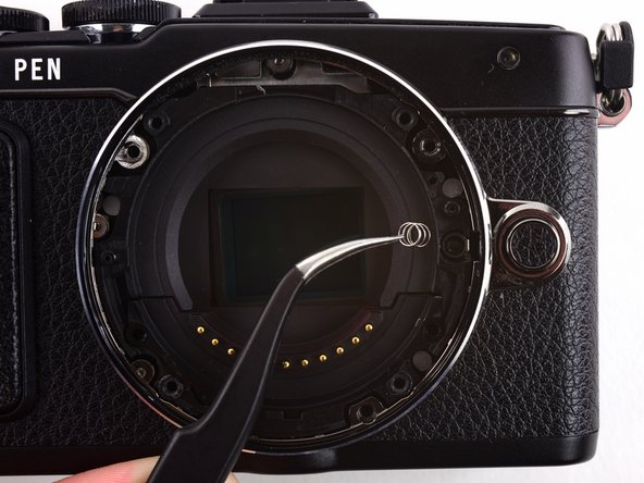 Image 3/3: Use tweezers to remove the spring underneath the lens hook.