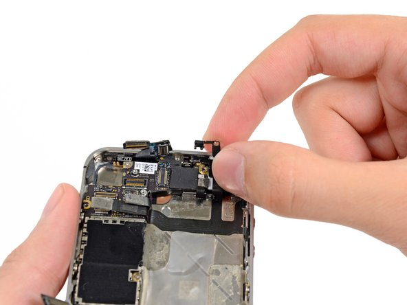 Carefully grasp the grounding clip and remove it from the iPhone.