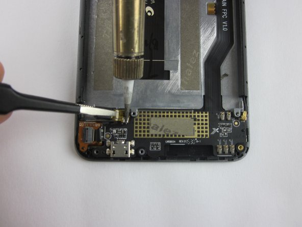 Using a soldering iron, simultaneously heat the two soldered connections for the motor